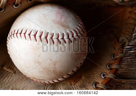 A close up image of an old used baseball and leather baseball glove.
