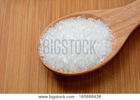 mono-sodium glutamate in wooden spoon and on wooden table