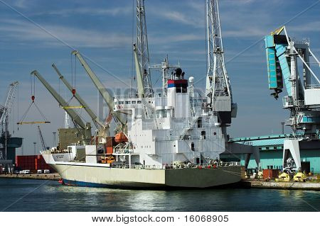 Cargo ship being unloaded at Antwerp harbor (all brand names and logos have been removed)