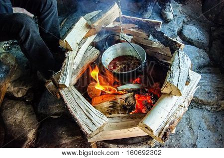 Outdoor cooking.Food in a cauldron on a fire.Tourist pot over the flame.Kettle on hanging around a bonfire.Camping kitchenware.