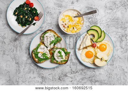 Delicious breakfast - fried egg poached eggs avocado spinach salad muesli and cheese sandwiches on light surface top view