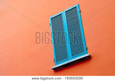 window on orange wall with closed blue blinds