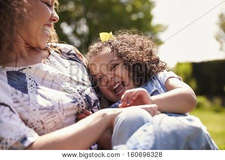 Mother tickling her daughter, sitting in a garden