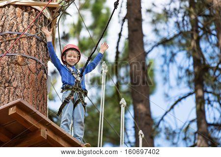active brave little boy enjoying climbing at treetop adventure park