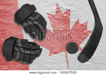 Canadian ice hockey stick gloves and puck on the ice. Concept