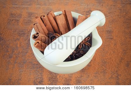 Fragrant Anise, Cloves, Cinnamon Sticks In Mortar On Rustic Board