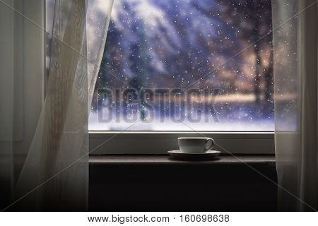 Cup on the windowsill. Outside winter fairy tale - the evening a beautiful snow falls. The concept of comfort in the home loneliness winter evening