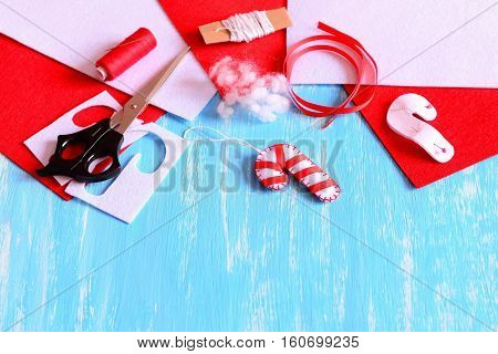 Christmas tree candy cane decoration made of white felt and red ribbon. Felt candy cane crafts, sewing materials to create Christmas tree decorations. Blue wooden background with empty place for text