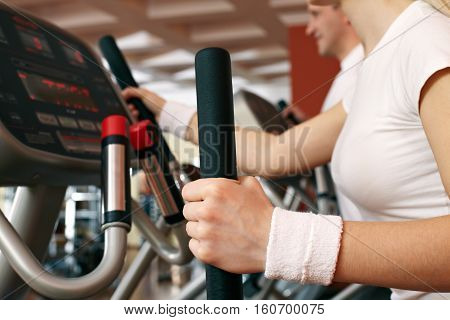 Close-up of female hand on lever of exercise machine at gym