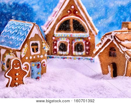 Three fabulous gingerbread house for Christmas. Gingerbread man winter foreground. Snowfall and Christmas. Food concept.