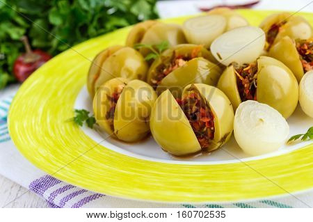 Pickled green tomatoes stuffed with a mixture of chopped garlic parsley chili pepper. Spicy appetizer on a white background. Close up
