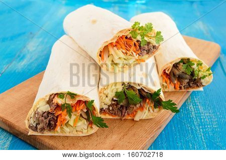 Shawarma sandwich - fresh roll of thin lavash (pita bread) filled with grilled meat mushrooms cheese cabbage carrots sauce green. Traditional Eastern snack. On a blue wooden background.
