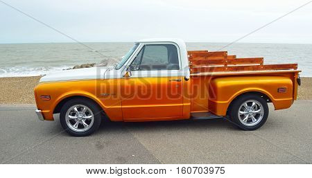 FELIXSTOWE, SUFFOLK, ENGLAND - AUGUST 27, 2016: Classic Gold and white pickup truck on seafront promenade with sea in background