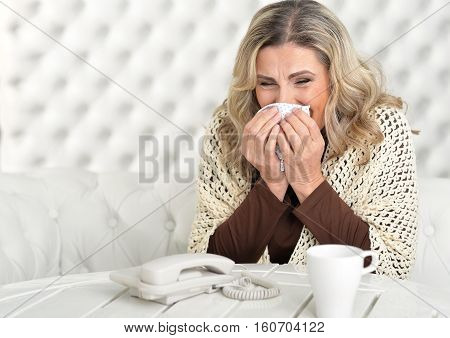 Portrait of Sick mature woman sitting at the table with handkerchief
