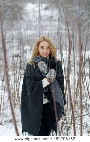 Blond girl in a gray poncho and white sweater posing outside in winter