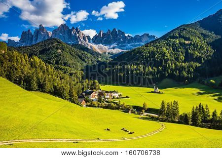 Little church of Santa Maddalena in Val di Funes.  Sunny autumn day in Dolomites, Tirol. Rocky peaks and forested mountains surrounded by green Alpine meadows