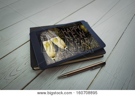 Tablet and pen on desk against composite image of champagne flutes clinking