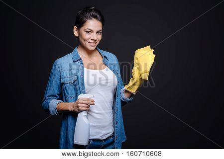 I enjoy the cleanliness. Delighted smiling young woman holding a glass cleaner and a duster while wearing rubber gloves and standing isolated in black background