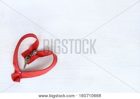 red clothes lightning with keychain key on light wood surface top view / heart open to love