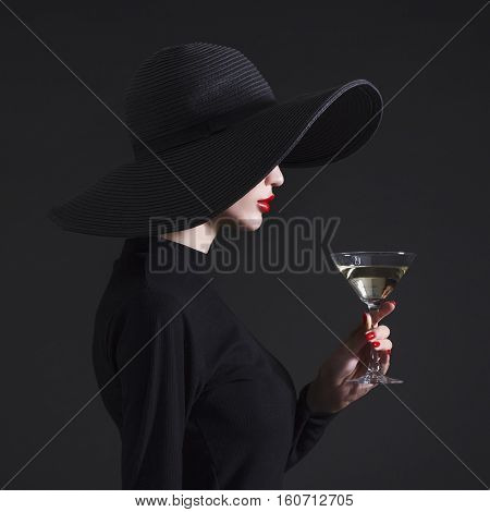 Luxury woman in a large black hat and bright lips with a glass of Martini.