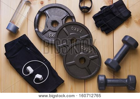 Top view of accessories for fitness in black grey tone. Dumbbells weight plates gloves for gym sport watchmusic player and bottle of water on wooden background. Concept for sport or workout.