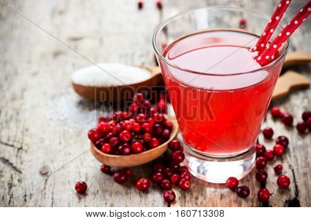 Glasses of fresh cranberry drink on wooden background. Red bilberry whortleberry huckleberry cowberry foxberry lingberry lingonberry mountain cranberry lingenberry berry cocktail wine liqueur