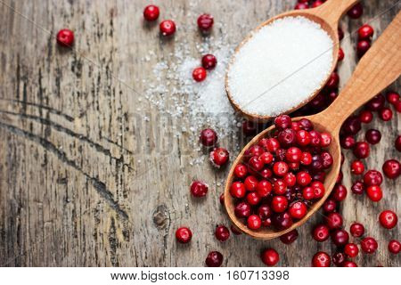 Fresh cranberry and sugar in spoons for homemade cranberry candy or drink liquor drink wine on wooden background top view