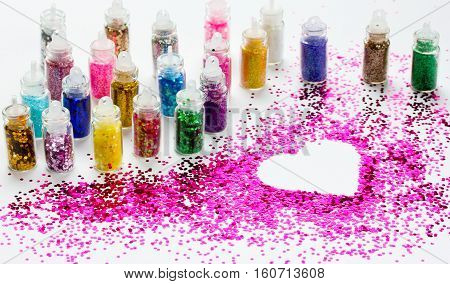 Lot colored glitters make-up in a small bottle on a white background