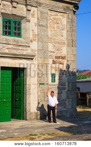 O PEDROUZO SPAIN - AUGUST 15: Man ring the bell of the Santa Eulalia church on August 15 2016