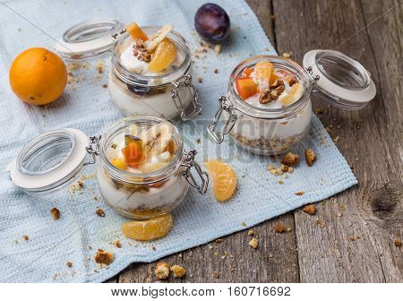 Healthy breakfast overnight oats with fresh fruit in a glass jar on wooden background