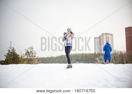 Woman Holding Her Pet Dog In Her Arms. Spitz Breed Dog Playing With Woman Walking Outdoors Winter Da