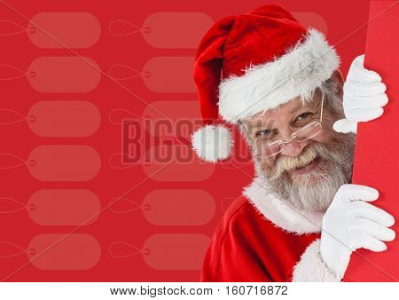 Smiling santa claus peeking from behind the wall against red background