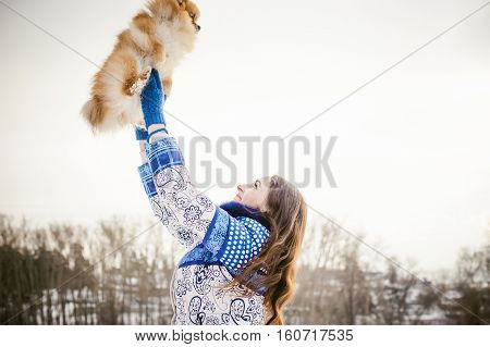 Smiling Woman Holding Her Pet Dog In His Hands Near Face, Tossing Up Overhead. Spitz Breed Dog Playi