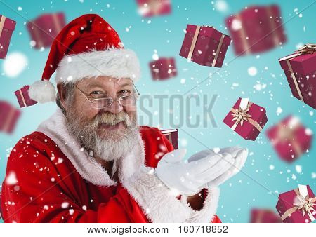 Portrait of santa pretending to hold digital generated christmas gifts against blue background