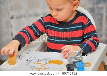 little cute boy draws  paints and fingers