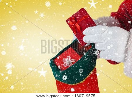 Santa putting gifts in christmas stocking against digitally generated yellow background