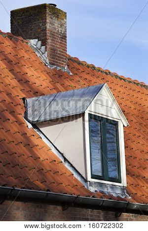 Old picturesque red tiled roof with dormer and chimney in the Netherlands