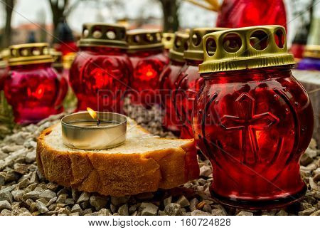 Uzhgorod Ukraine - 26 November 2016: A slice of bread with candle among gravelights while honoring the memory of Holodomor victims.