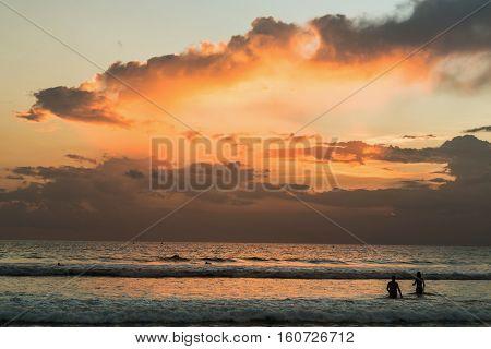 Beautiful sunset of Kuta Beach Bali Indonesia. Silhouettes of people at sunset on Kuta beach in Bali Indonesia