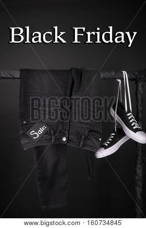 Black Friday. Sale Sign.  And White Sneakers  Pant, Jeans Hanging On Clothes Rack   Background.  Clo