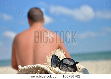 Young Man With Sun Cream On His Back Stands To Sunbath On The Beach, Focus On The Straw Hat And Glas