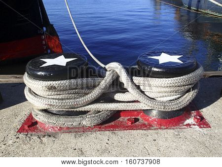 Ships mooring post to tied up vessels in port with ropes secured on them