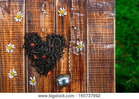 Vintage Strainer Near Dry Leaves Of Black Tea Make In Heart On Wooden Table In Garden And  Nature Ba