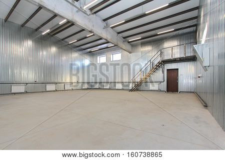 empty light parking garage warehouse interior with large white gates and windows inside
