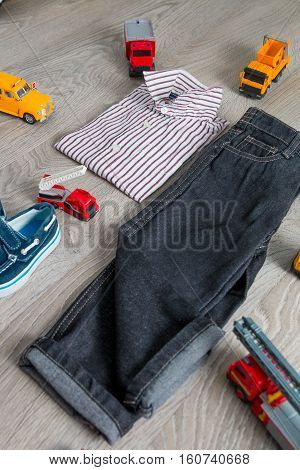 Boy Outfit Near Car Toy. Striped Shirt, Denim Pants And Blue Boat Shoes  Yellow  Red Cars. Back View