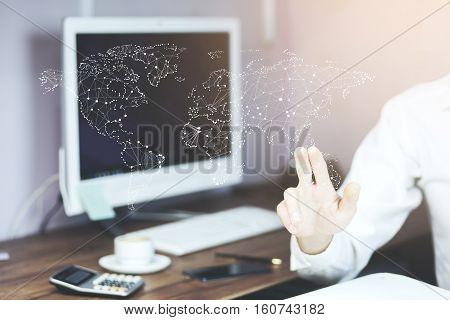 Man touching virtual world map by hand