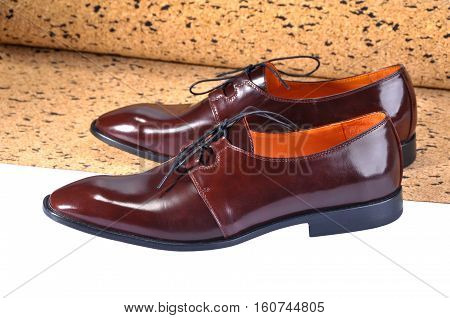 Men's Classic Leather Shoes with a slim elongated toe made from a smooth brown leather. standing on a sheet of balsa wood