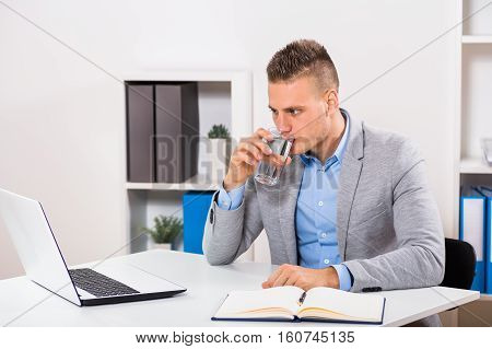 Businessman is drinking water and working in his office.