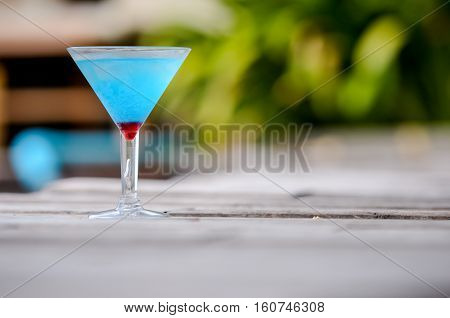 Frozen Blue Margarita Cocktail, blue cocktail on the wooden table, blurry background