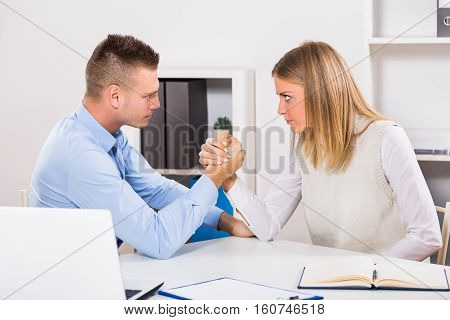 Arm wrestling between businessman and businesswoman at work.